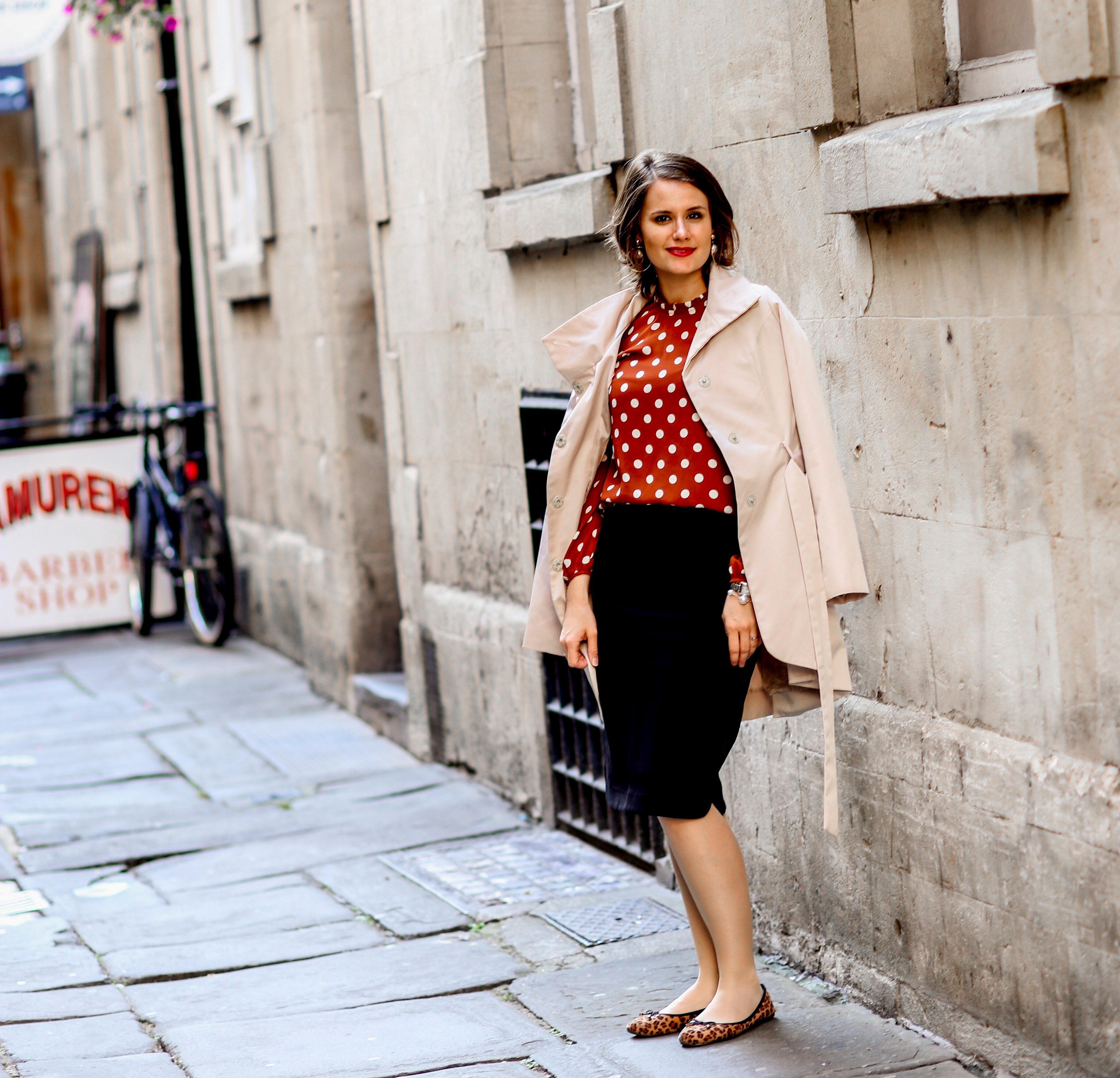 Rust polka dot blouse, black pencil skirt, beige trench coat and leopard print shoes